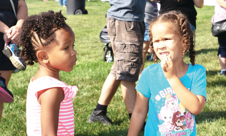 Siena Posey, right, and her sister Laniyah, both 5, of Northglenn, await entrance to a large bounce house at the Thornton Harvest Fest, Sept. 9, at Thornton Community Park.