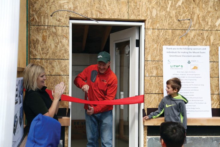 David Epp, principal of Mt. Evans Outdoor Lab, cuts the ribbon on the soon to be completed greenhouse.