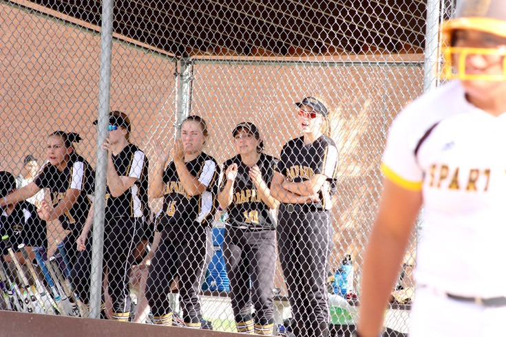 Arapahoe High School softball players cheer on their teammates in the field as a Thomas Jefferson player prepares for an at-bat on Sept. 15. Arapahoe won 6-5.