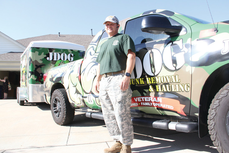 Hank McClellan stands in front of his hauling truck and trailer Sept. 12 after finishing an early-morning job. JDog Junk Removal, a company started in 2011 in Pennsylvania by a military veteran, has spread to 35 states since starting to franchise in 2012.