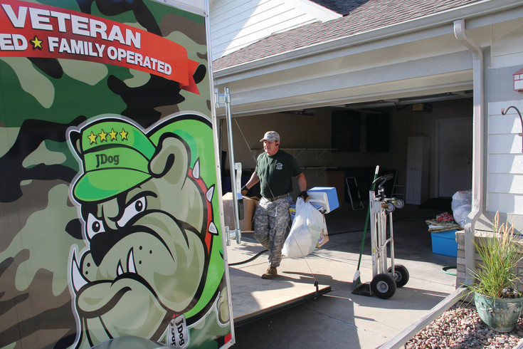 Hank McClellan, owner and operator of a JDog Junk Removal franchise in Centennial, clears out a customer's garage in Aurora Sept. 12. McClellan, a 33-year military veteran, started the franchise in July after retiring from military service.