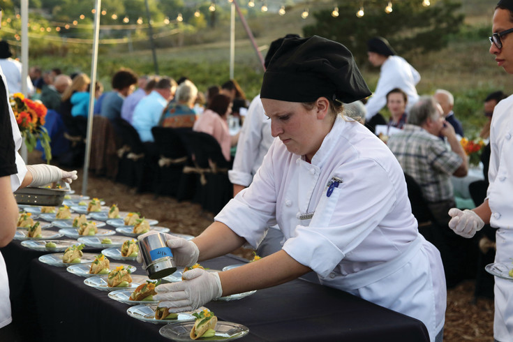 Warren Tech culinary student Brianna Gregory helps put the finishing touches on the first course of the seven-course meal.