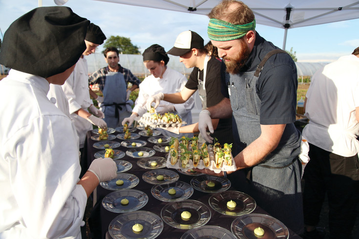 Chef Blake Edmunds plates his dish, a cucumber tart with spicy crema and edible herbs and flowers.