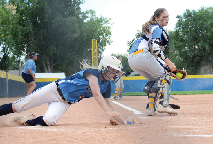 Ralston Valley senior Haley Bass, left, slides around Wheat Ridge catcher Kate Anderson on Sept. 12, in an electric game that saw both teams hitting well.  The Farmers took the 9-7 victory.