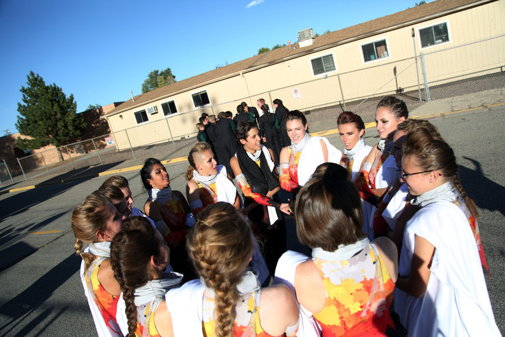 Members of the D'Evelyn High School winter guard have a pep talk before taking the field with the marching band.