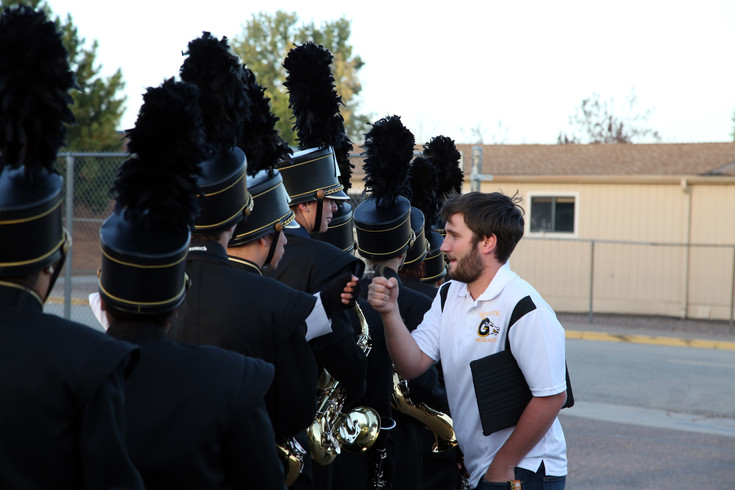 Patrick Clark fist bumps members of the Green Mountain High band before they take the field.