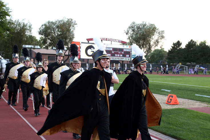 Drum Majors Zack Valencia and Rachel Bales lead the Green Mountain Marching band onto the field.