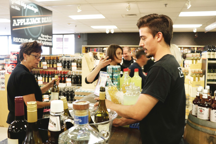 Applejack employee Taylor Butel pours drinks for customers during an event at the liquor store last year. Store management is alleging that a rival liquor store was given access to sensitive business information by the city of Wheat Ridge.