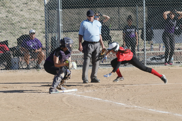 Paige Burke dives head first into home plate to score a run for Elizabeth during the Sept. 21 league softball game against Mesa Ridge. Burke was safe and the Cardinals retained a share of first place in the league as they outscored the Grizzlies, 9-4.