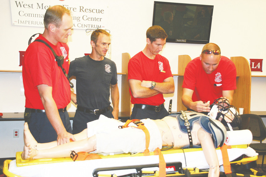 West Metro Fire Rescue's EMTs and paramedics familiarize themselves with the latest equipment and gear football players use during an Aug. 18 training session. The fire department worked with emergency room doctors from St. Anthony Hospital to help prepare for responding to injuries commonly seen during football season.
