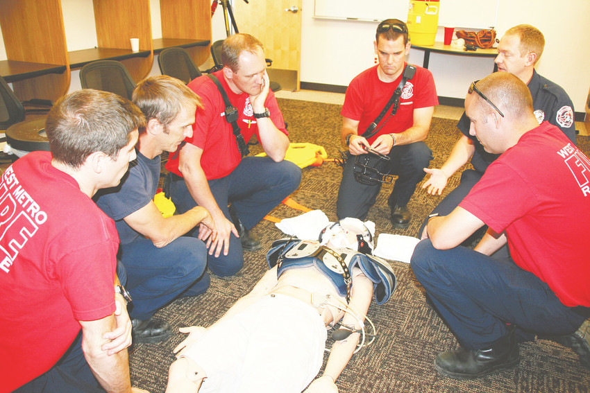 EMTs and paramedics with West Metro Fire Rescue train on a dummy on how to best respond to an injured football player on Aug. 18. About 280 members of the West Metro Fire Rescue team receive the hands-on training, which spanned a three-week time period, to coincide with the start of this year's football season.