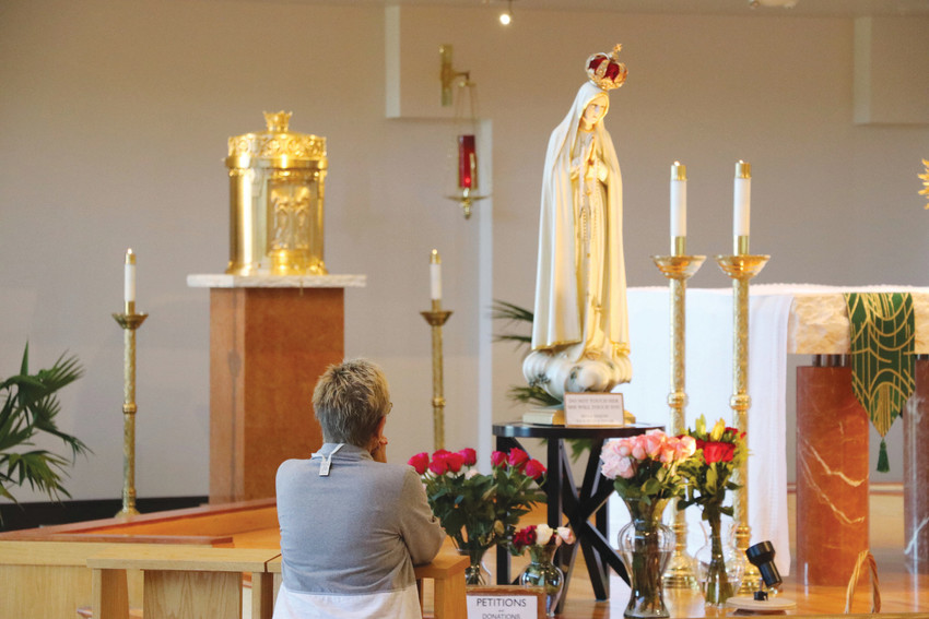 A woman prays at a Sept. 21 visit from International Pilgrim Virgin Statue of Fatima, a 3-foot statue that represents Virgin Mary, at St. Mark Catholic Church,  9905 Foothills Canyon Blvd. The statue  has made appearances at the local church twice this year.