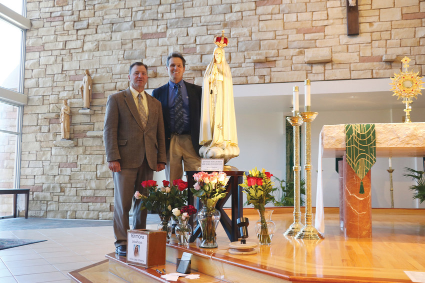 Statue custodians Larry Maginot, left, and Tom Ross stand beside one of two International Pilgrim Virgin Statues of Fatima. The men and statue have been traveling in an RV across the country, stopping at local churches, since spring of 2016.