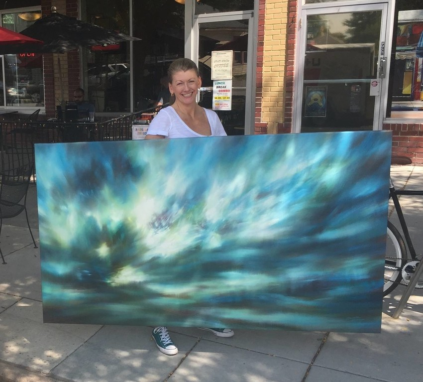 Painter Danielle Hatherley carries one of her large canvases into Westward Gallery in the Berkeley area of Denver for a September show.