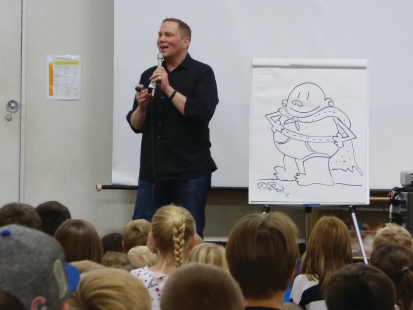 Captain Underpants author Dav Pilkey beside a sketch of his signature character at Lenski Elementary School.