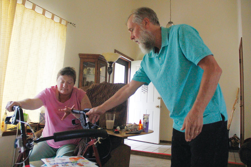 Cindy Cummins reaches for her walker as her husband Chris assists her. Chris has been Cindy's primary caregiver since she was diagnosed with multiple sclerosis in 2005, a role he says forced him to confront his own misconceptions about marriage, devotion and entitlement.
