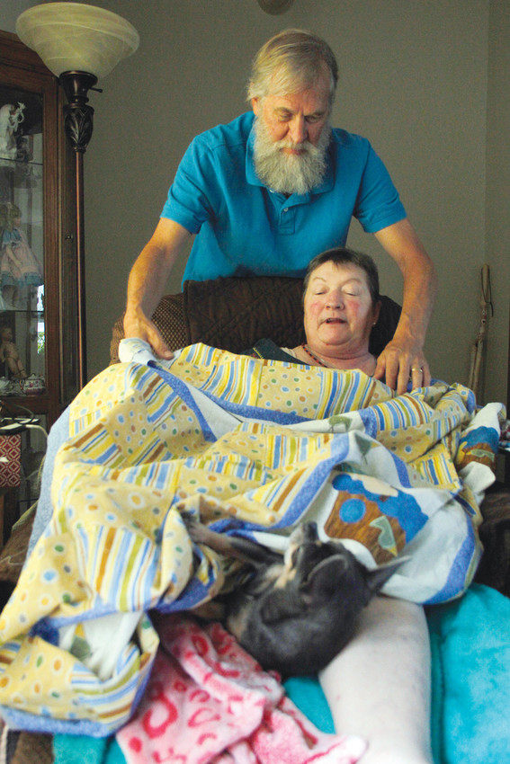 Chris Cummins helps his wife Cindy with one of her handmade quilts, rousing Cindy's Chihuahua, Porscha. Cindy's creativity, apparent in the quilts she's made for decades, was one of the attributes that attracted Chris, himself a writer and amateur musician, to her.