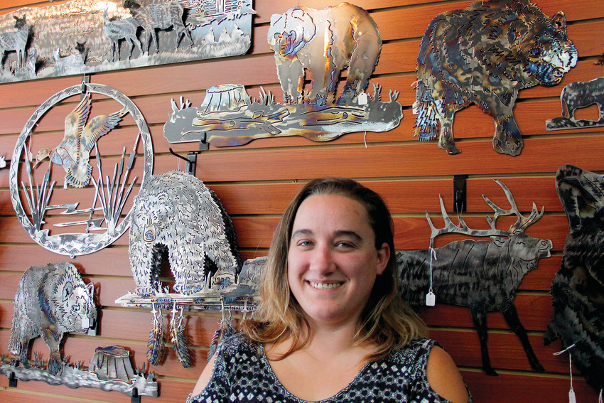 Cassie Franklin stands before a display of finished steel artwork in the Cassteen Ironworks store in the shopping plaza at the intersection of Mainstreet and Parker Road. The store deals in custom artwork and furnishings like chairs, benches and window well covers.