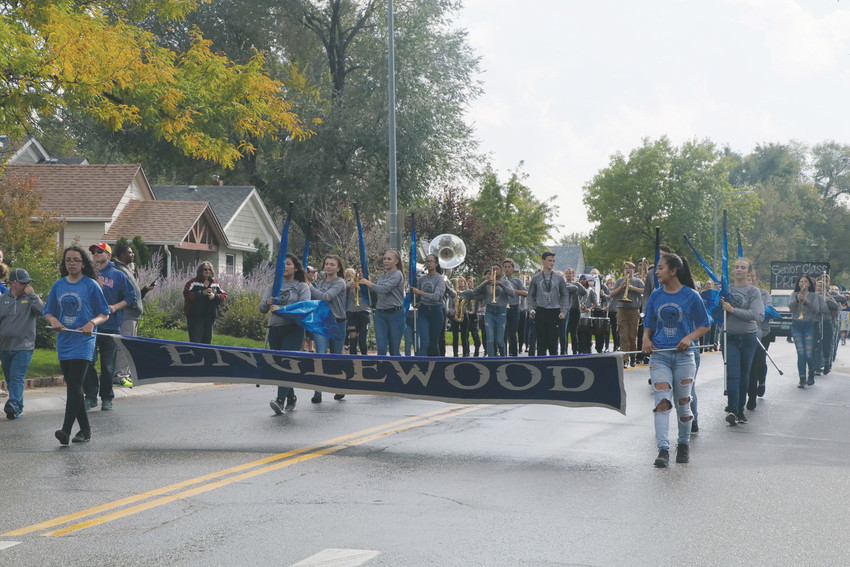 The Englewood High School band marches down South Logan Street and prepares
