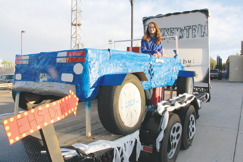 "Senior Haley Eickmann stands atop the senior class' float at the Englewood High School tailgate event before the homecoming football game Oct. 6. ""For three years, we've won best float,"" Eickmann said. ""So we're trying to"" win again. Eickmann came up with the float's drive-in theater theme."