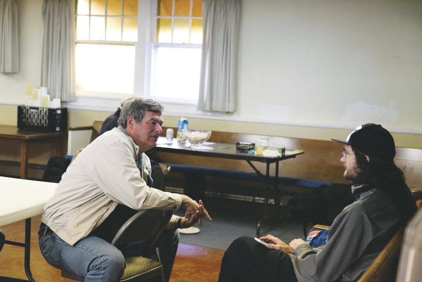 Steve Byers, pastor of The Rising Church in Olde Town Arvada, talks with a newly homeless man getting services at the church's new day shelter.