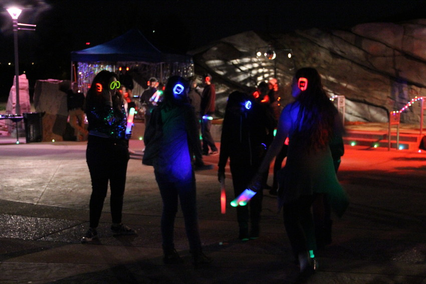 Teens on the dance floor at Centennial's silent disco in Centennial Center Park Oct. 6. Attendees got light-up sticks and light-up headphones and glasses.