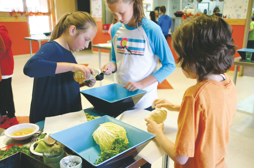 Oskar Bech-Truemen, an 11-year-old from Rocky Heights Middle School, rolls dough while Maddy Klein, left, and Jordan Kolbjay, both from Eagle Ridge Elementary School, measure oil. The three students were making pork dumplings at a fall break culinary camp on Oct. 11 at Stone Canyon Outdoor Edventures, 12163 S. Perry Park Road, Larkspur.