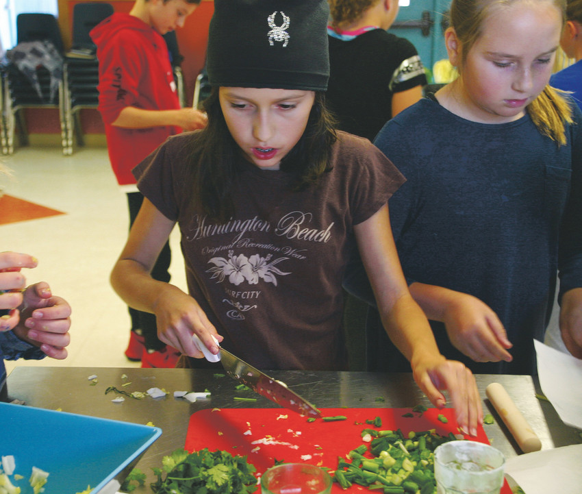 "Danielle Barron, a 12-year-old from Clear Sky Elementary in Castle Rock, demonstrates her cooking skills as she chops chives at culinary camp on Oct. 11 at Stone Canyon Outdoor EdVentures, 12163 S Perry Park Road, Larkspur. ""I just like working with my friends,"" Barron said."