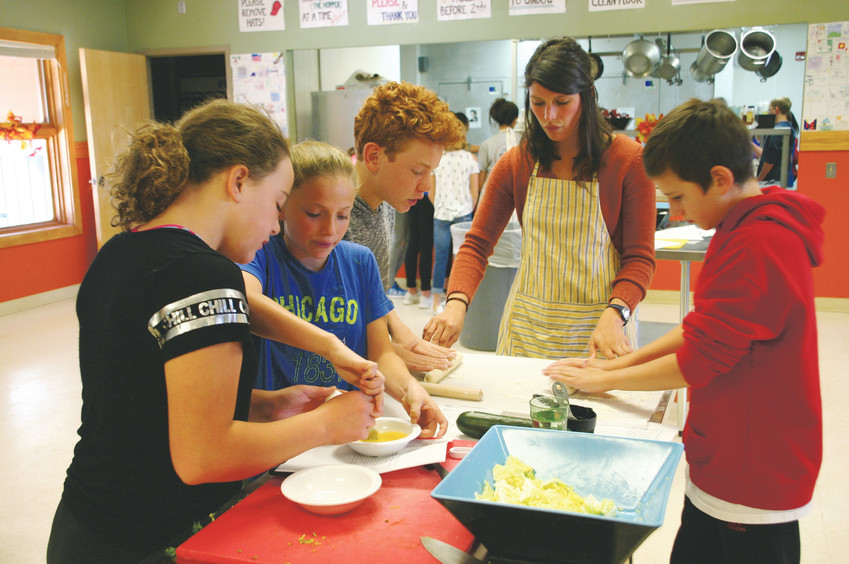 Middle school students from across Douglas County use teamwork to make pork dumplings at culinary camp on Oct. 11 at Stone Canyon Outdoor EdVentures, 12163 S Perry Park Road, Larkspur. The group's teacher, Brittany Graham, in the striped apron, used to teach culinary classes in Baltimore, Maryland.