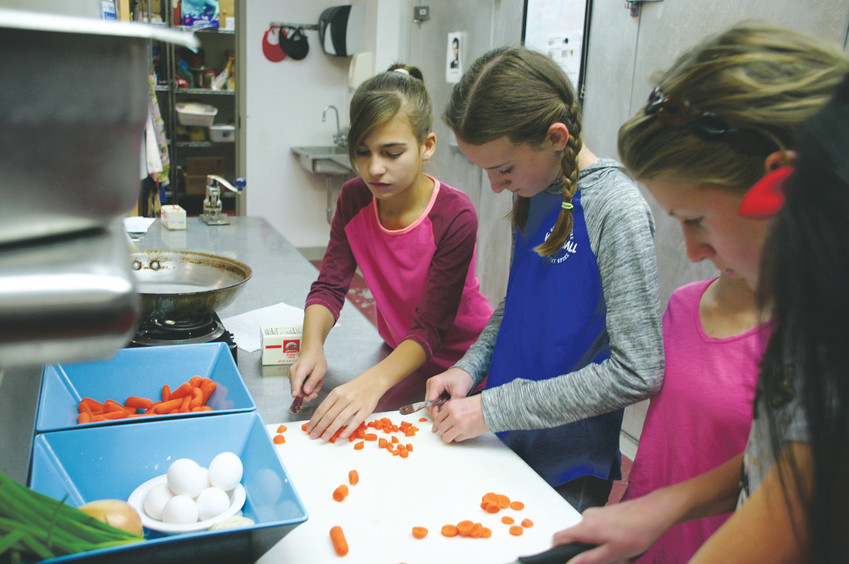 Students prepare veggies for chicken fried rice, which will accompany pork dumplings, at culinary camp on Oct. 11 at Stone Canyon Outdoor EdVentures, 12163 S Perry Park Road, Larkspur.