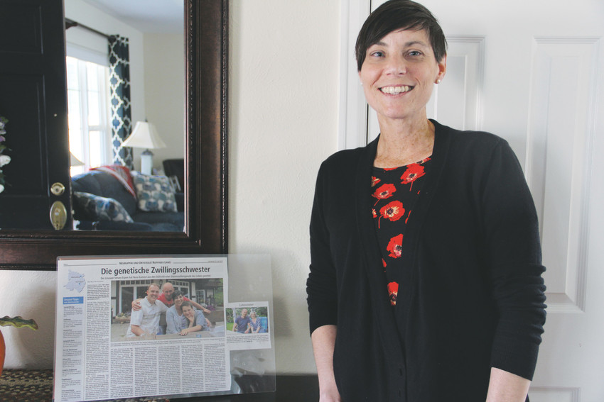 Nora Earnest, a cancer survivor and founder of The Earnest Scholarship Fund, stands in her Centennial home Oct. 4 next to a laminated German newspaper article about her and her once-anonymous stem cell donor whose donation saved her life. A trip to the mountains she took with her family during her years of treatment was so significant to her that she started a nonprofit fund with her husband in 2011 to help other cancer patients do the same.