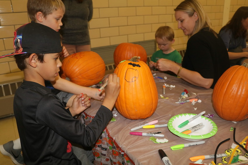 Eli Williams uses a marker to color one of the eyes on the face he is created on the pumpkin his parents bought at the Oct. 12 Charles Hay World School Harvest Festival. Williams, 6, joined a table full of kids taking advantage of the opportunity to decorate their pumpkin for Halloween.
