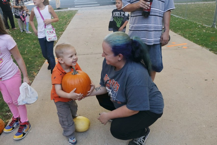 Henry Parks shows his mother Michelle the pumpkin he wants her to buy for him. The 3-year-old and his parents were among about 300 people who attended the Oct. 12 Charles Hay World School Harvest Festival.