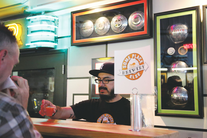 Paul Aguirre serves samples from Someplace Else Brewery in Arvada.