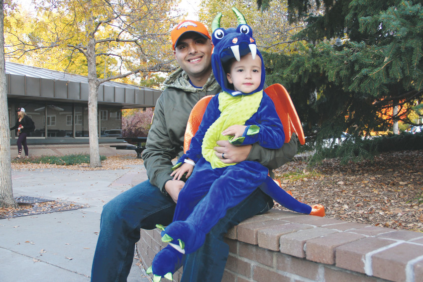 Mike Kitsmiller, 31, holds son Easton Kitsmiller, 3, outside the Spooktacular event in Centennial Oct. 13. Easton Kitsmiller dressed as a dragon and elicited comments of awe from other passing children.
