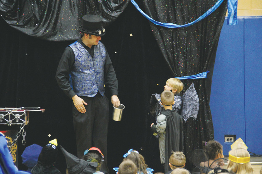 A magician talks to kids on stage as he performs tricks for the crowd of dozens of children at the Spooktacular Oct. 13. Parents sat around the crowd too, and some parents came in costume.