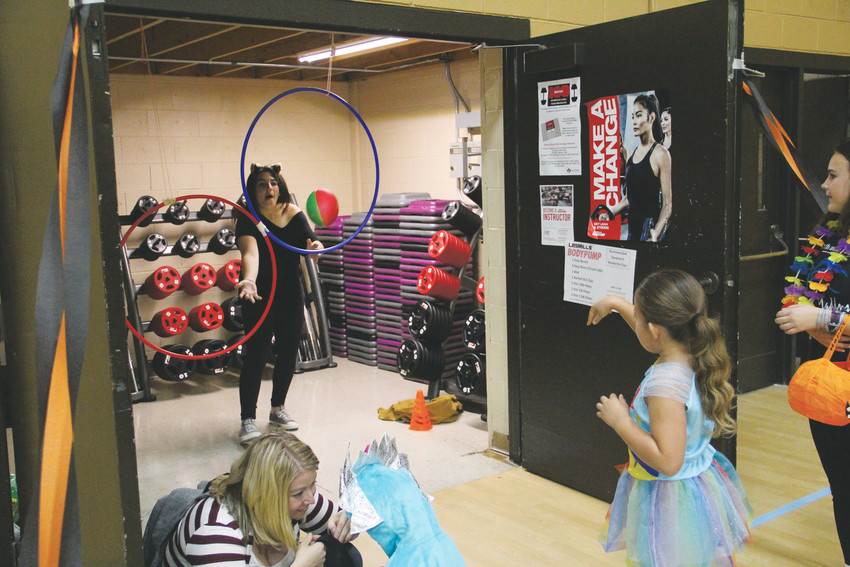 A girl throws a football through a suspended hula hoop to another girl supervising the station at the Spooktacular Oct. 13. After completing the activity — one of many around the gym — kids got Halloween candy from a bag.