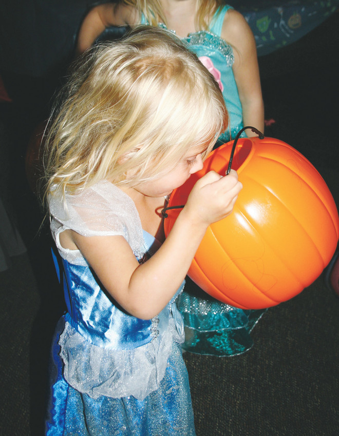 Quincy Grissom, 3, aka Cinderella, looks in her pumpkin bucket to check out the treats she's received at Golden High School's trick-or-treat street on Oct. 18.