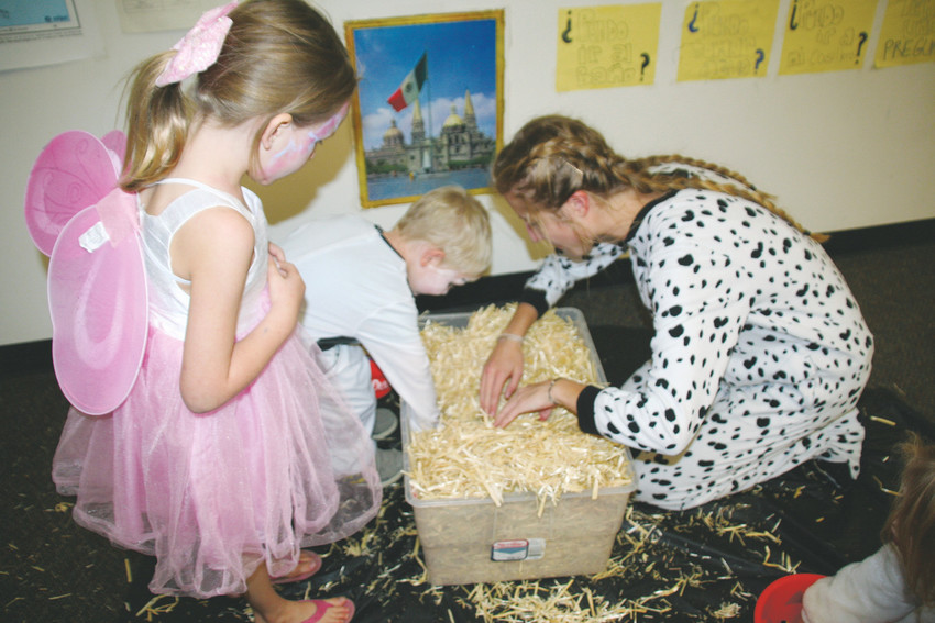 Lina Wise, right, a junior at Golden High School, assists Dylan Carney, 3, with digging through straw in search for a prize as his sister, Abby, 5, looks on. The game was the French club's contribution to Golden High School's trick-or-treat street on Oct. 18.