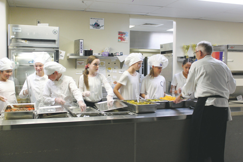 Chef Chuck Stober, from the Escoffier Culinary School in Boulder, directs students as they prepare to serve more than 100 guests.