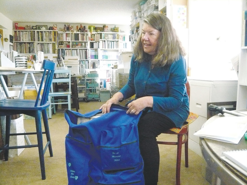 Pat Clarke- Watercolorist/plein air painter Pat Clarke, in her Highlands Ranch home studio. She displays the special painters' backpack her daughter made for her to carry supplies while working outdoors. Photo by Sonya Ellingboe.