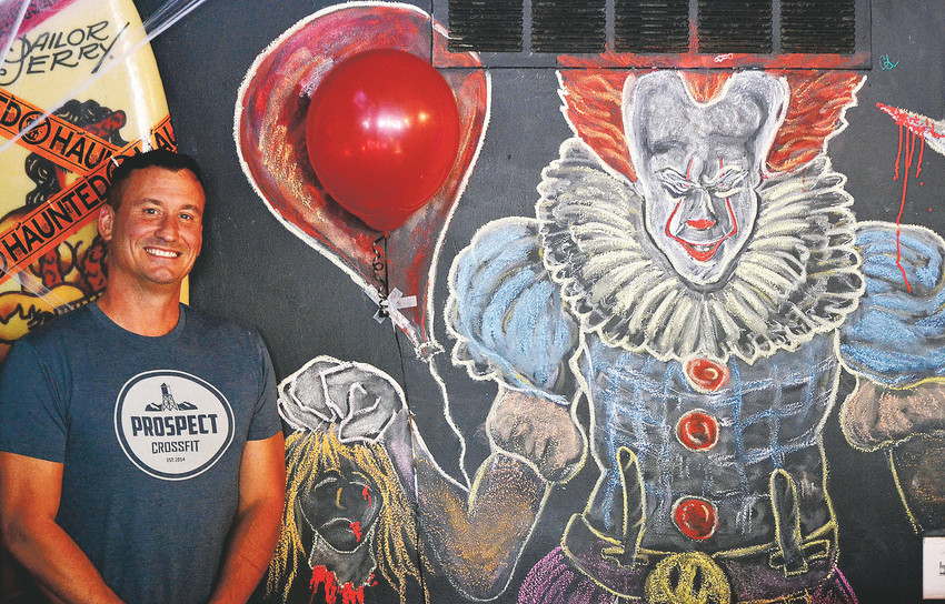 "Chris Schulte is the man behind the chalk in drawing art on the wall behind the bar at Cheapskates in Olde Town Arvada. Schulte is pictured here with his latest artwork: a rendition of Pennywise from ""IT."""