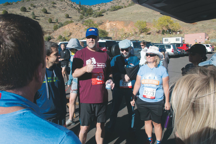 John Brackney, middle wearing number 42, talks with teammates at the Oct. 8 Run the Rocks event at Red Rocks Park. Brackney, a Centennial resident, has run at the event for eight years in a row.