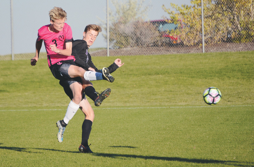 Ralston Valley senior Kyle Sterns (3) gets off a shot despite the efforts of Arvada West sophomore Keegan Nelson on Oct. 17 at the North Area Athletic Complex. The Mustangs won 4-1 on their way to a second straight Class 5A Jeffco League title.