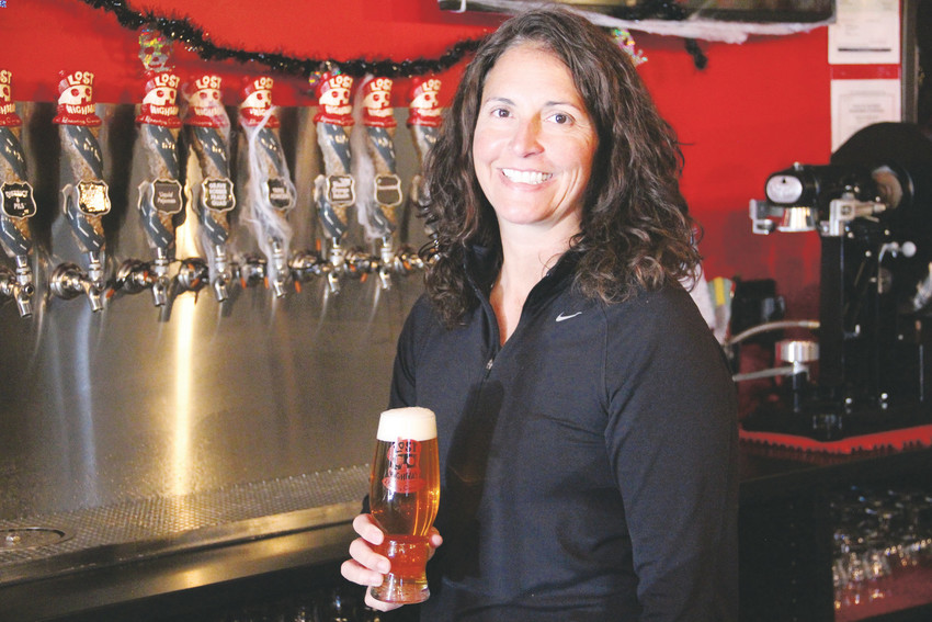 Tina Pachorek, co-founder of Lost Highway Brewing Company in Centennial, stands with a beer at the business Oct. 17. Pachorek, who's lived in Centennial since 2001, has been in the industry for 15 years.