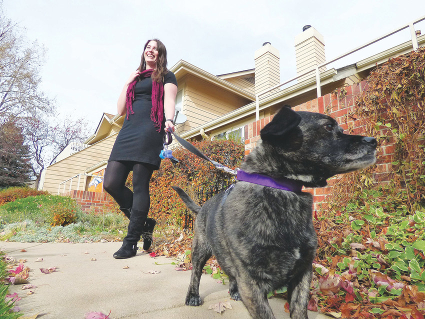 Lacy Franks and her 8-year-old sausagehound Pepper in front of their townhome. Franks bought the home last year with savings she originally intended to spend on medical school.