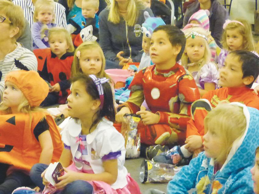 Mini superheroes and princesses settle in for storytime with children's librarian Shannon Brennan.