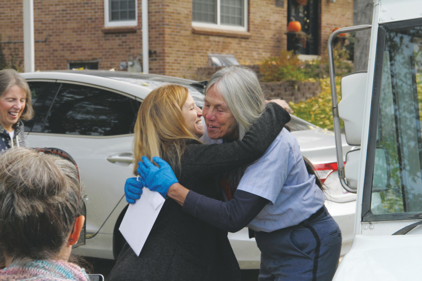 A resident in the Homestead Farm neighborhood of Centennial embraces Ellen Nelson, a United States Postal Service mail carrier, on her last day before retirement Oct. 27. Nelson is 64.