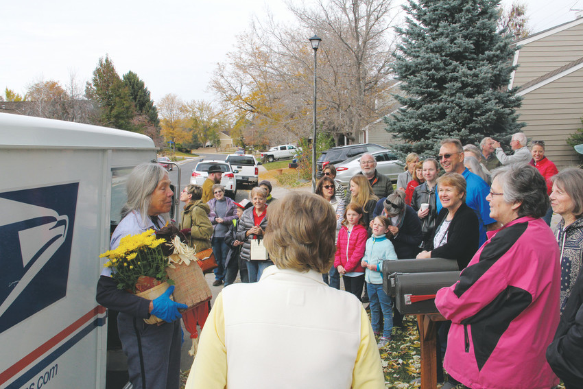 Dozens of neighbors in the Homestead Farm neighborhood of Centennial gather to celebrate mail carrier Ellen Nelson on her last day on the job, Oct. 27. Nelson, a postal worker for nearly three decades, served the neighborhood for 14 years.
