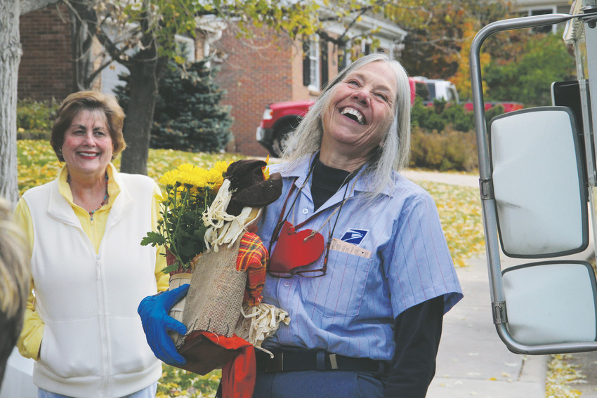 Mail carrier Ellen Nelson laughs during a surprise celebration on her last day before retirement, Oct. 27. Dozens of residents in the Homestead Farms neighborhood gathered along her mail delivery route to say goodbye.